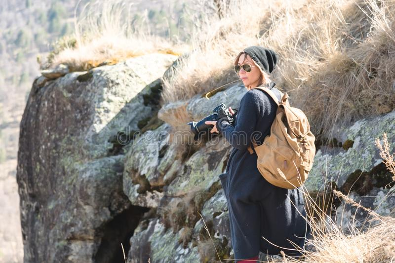 Hipster-φωτογράφος γυναικών με τη κάμερα dslr Μοντέρνο κορίτσι στα γυαλιά ηλίου με μια κάμερα στη φύση στοκ εικόνα