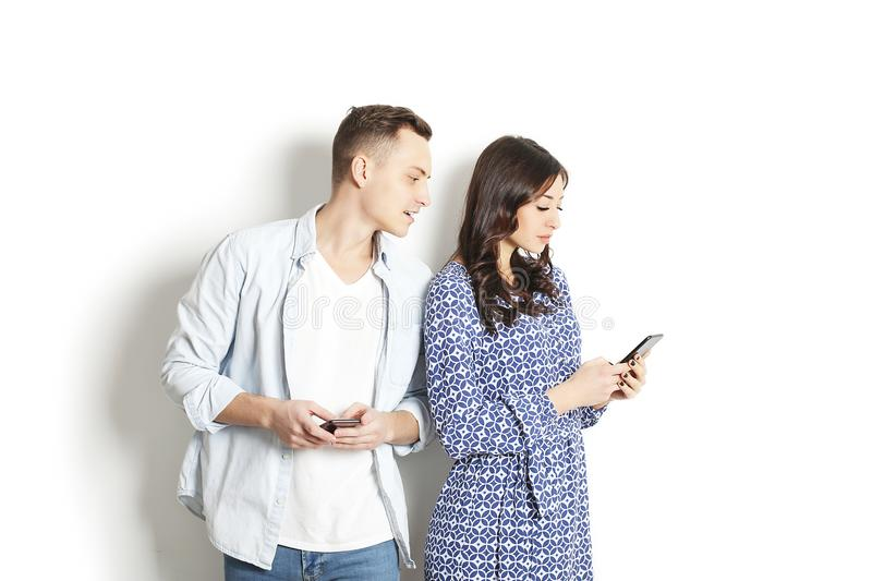 Jealous husband spying his wife mobile phone while she is reading a message. Technology & relationship concept. Modern romance tro stock photography