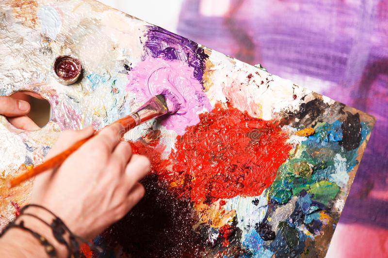 Hipster Artist With Palette. Caucasian hipster artist putting purple paint on his palette in the studio stock images