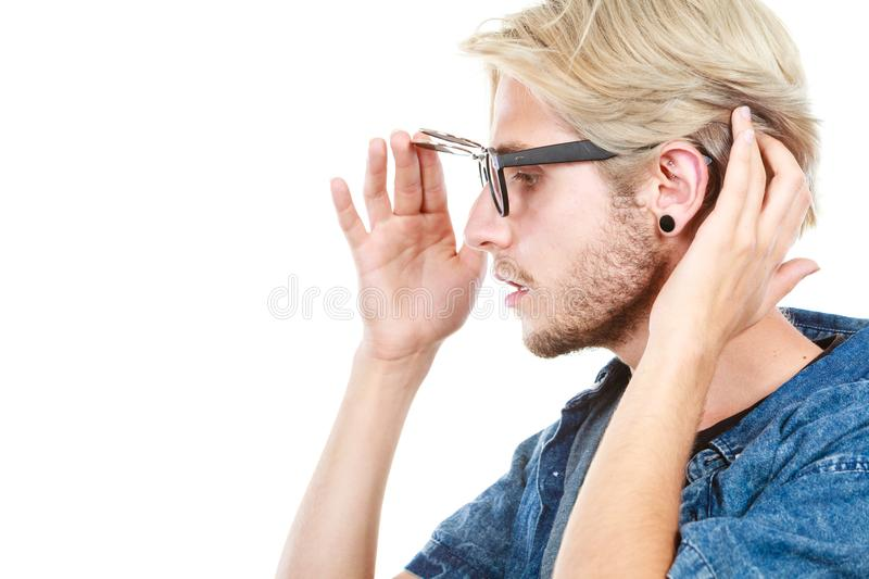 Hipster artistic man with eccentric glasses, profile portrait. Men fashion, accessories, hairstyle, modeling concept. Artistic hipster blonde man wearing royalty free stock images