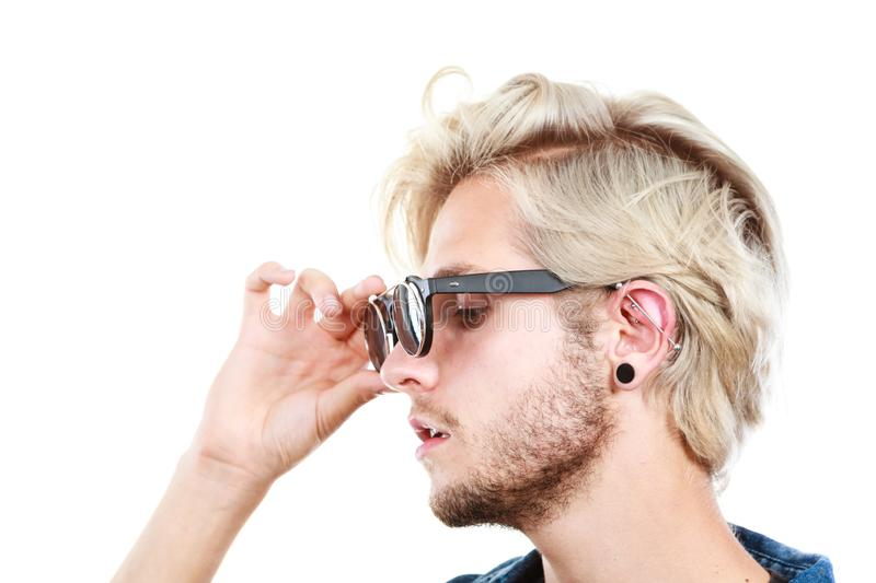 Hipster artistic man with sunglasses, profile portrait. Men fashion, accessories, hairstyle, modeling concept. Artistic hipster blonde man wearing and holding stock image