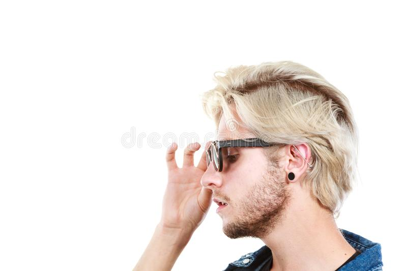 Hipster artistic man with sunglasses, profile portrait. Men fashion, accessories, hairstyle, modeling concept. Artistic hipster blonde man wearing and holding royalty free stock photo