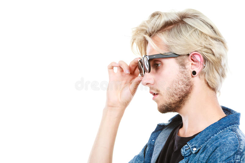 Hipster artistic man with sunglasses, profile portrait. Men fashion, accessories, hairstyle, modeling concept. Artistic hipster blonde man wearing and holding royalty free stock images