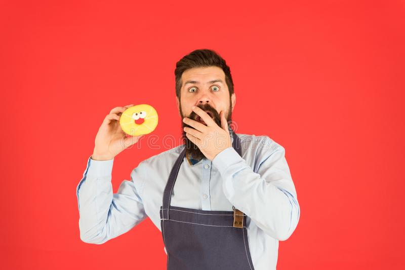 Hipster baker hold donuts. Cheerful mood. Doughnut calories. Glazed donut. Baked goods. Sweets and cakes. Junk food stock image
