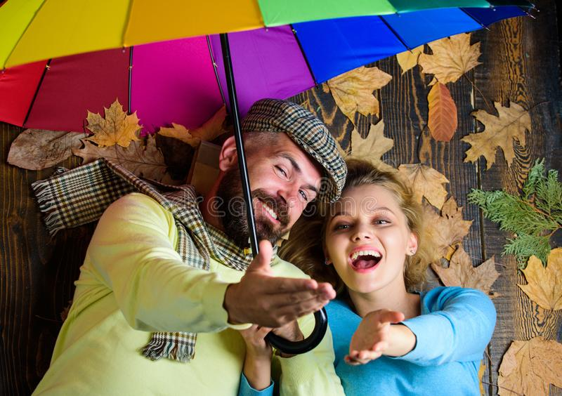 Hipster with beard and cheerful girl expect rainy weather hold colorful umbrella. Couple in love lay on wooden. Background top view. Romantic couple dating stock images