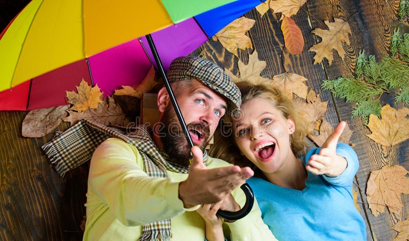 Hipster with beard and cheerful girl expect rainy weather hold colorful umbrella. Romantic couple dating. Rainy weather. Not obstacle for them. Couple in love stock images