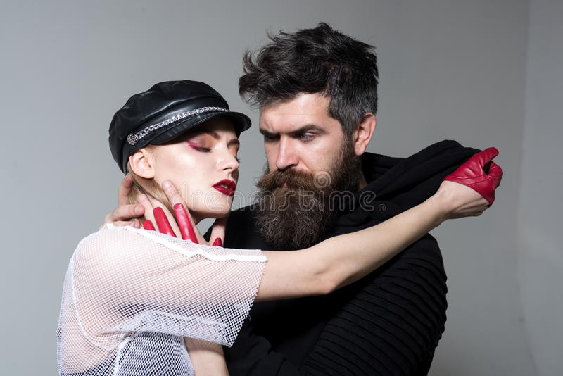 Hipster with beard and girl in leather cap and gloves. couple in love of woman and bearded man. rock couple embrace royalty free stock photography