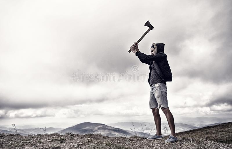 Hipster with beard holds axe while stand on top of mountain, sky on background, copy space. Lumberjack brutal and. Bearded raising axe. Man in hat and jacket stock photography