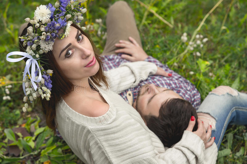 A loving couple of hipsters on walks. Hipster with a beard lies on the lap of his girl who wears a vinok of wildflowers. The concept of unity with nature and a royalty free stock image