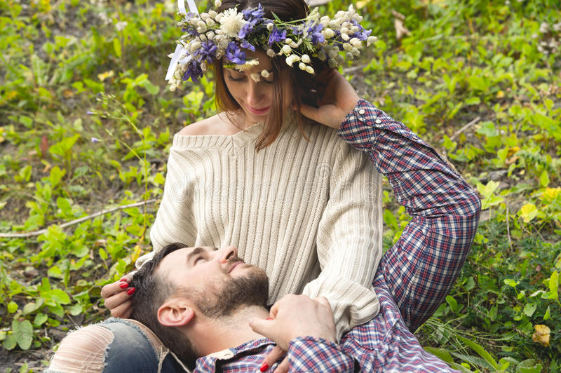 A loving couple of hipsters on walks. Hipster with a beard lies on the lap of his girl who wears a vinok of wildflowers. The concept of unity with nature and a stock photo