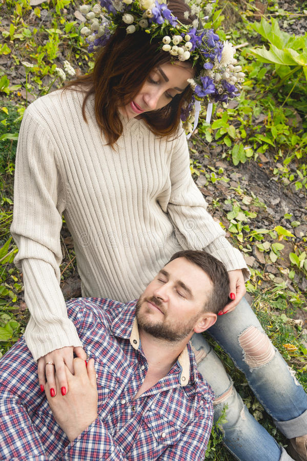 A loving couple of hipsters on walks. Hipster with a beard lies on the lap of his girl who wears a vinok of wildflowers. The concept of unity with nature and a stock photos
