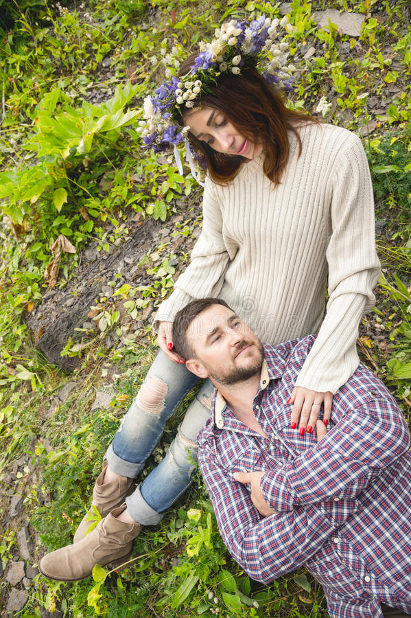A loving couple of hipsters on walks. Hipster with a beard lies on the lap of his girl who wears a vinok of wildflowers. The concept of unity with nature and a stock images