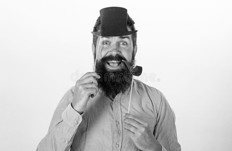 Hipster with beard and mustache on happy face posing with photo booth props. Guy smokes tobacco pipe. Aristocracy. Concept. Man holding paper party props royalty free stock photo