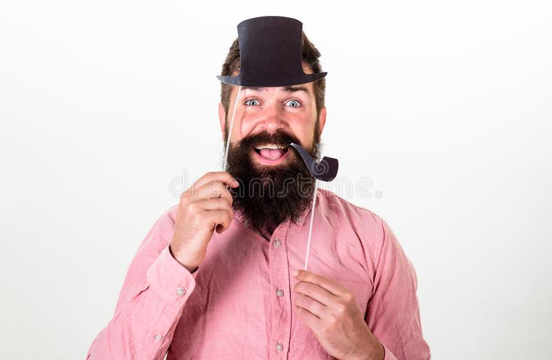 Hipster with beard and mustache on happy face posing with photo booth props. Guy smokes tobacco pipe. Aristocracy. Concept. Man holding paper party props royalty free stock photography