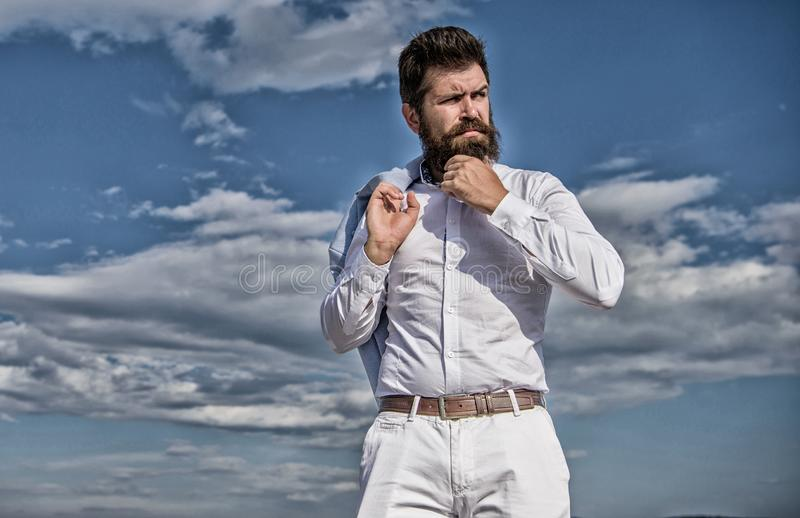 Hipster with beard and mustache looks attractive fashionable white shirt. Man bearded hipster formal clothes looks sharp. Sky background. Reached top. Guy enjoy stock photo