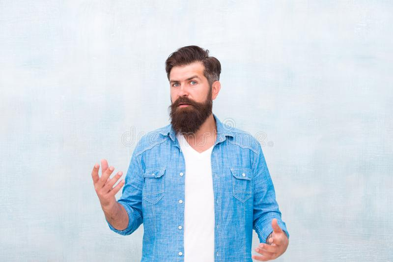 Hipster with beard and mustache wear denim shirt. Male beauty concept. Brutal handsome hipster man on grey wall. Background. Bearded man trendy hipster style stock photo