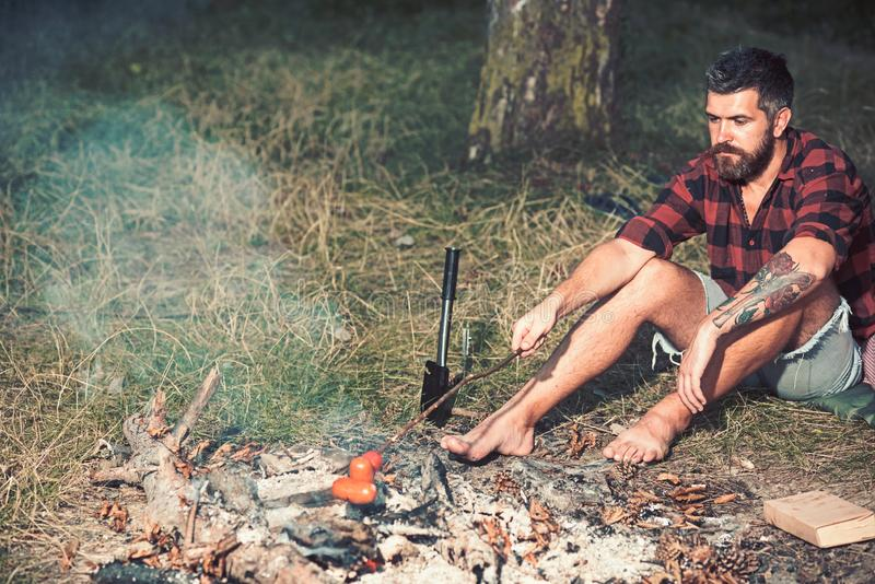 Hipster with beard roast sausage on fire. Bearded man cook food on bonfire. Man in plaid shirt relax on nature. Tourist. Enjoy camping. Summer vacation concept royalty free stock photo