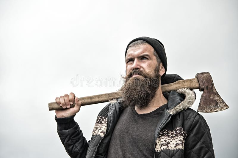 Hipster with beard on serious face carries axe on shoulder sky on background, copy space. Lumberjack brutal and bearded. Holds axe. Brutal lumberjack concept stock photography
