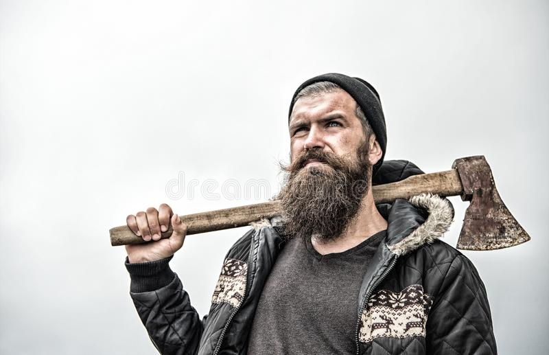 Hipster with beard on serious face carries axe on shoulder sky on background, copy space. Lumberjack brutal and bearded. Holds axe. Brutal lumberjack concept royalty free stock photography