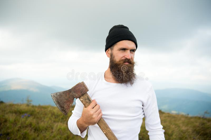 Hipster with beard on strict face holds axe, skyline on background. Lumberjack brutal and bearded holds axe while stand. On top of mountain. Hiking concept royalty free stock image