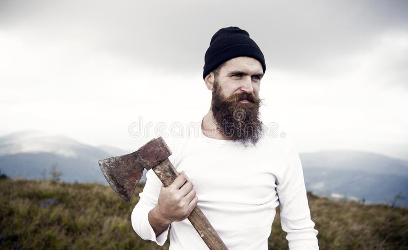 Hipster with beard on strict face holds axe, skyline on background. Lumberjack brutal and bearded holds axe while stand. On top of mountain. Hiking concept stock photo