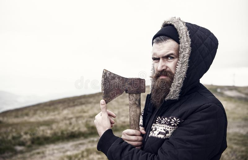 Hipster with beard on strict face holds sharp axe, skyline on background, copy space. Lumberjack brutal and bearded. Holds axe. Brutal lumberjack concept. Man royalty free stock photos