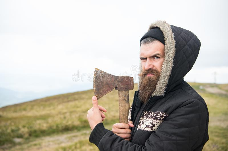 Hipster with beard on strict face holds sharp axe, skyline on background, copy space. Lumberjack brutal and bearded. Holds axe. Brutal lumberjack concept. Man stock photography