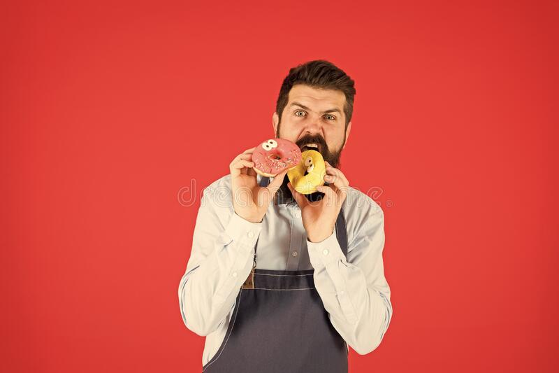 Hipster bearded baker eat donuts. Doughnut bakery. Bearded cheerful well groomed man selling donuts. Carbs and calories. Bakery owner. Bakery business. Baked stock photo