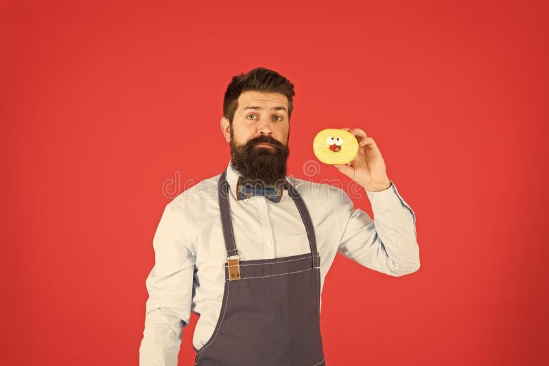Hipster bearded baker hold donuts. Eat donut. Cheerful mood. Doughnut calories. Glazed donut. Bearded well groomed man stock photo