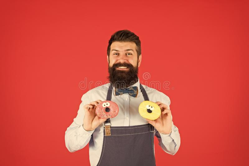Hipster bearded baker hold donuts. Sweet donut. Waiter in cafe. Doughnut calories. Glazed donut. Bearded well groomed royalty free stock photos