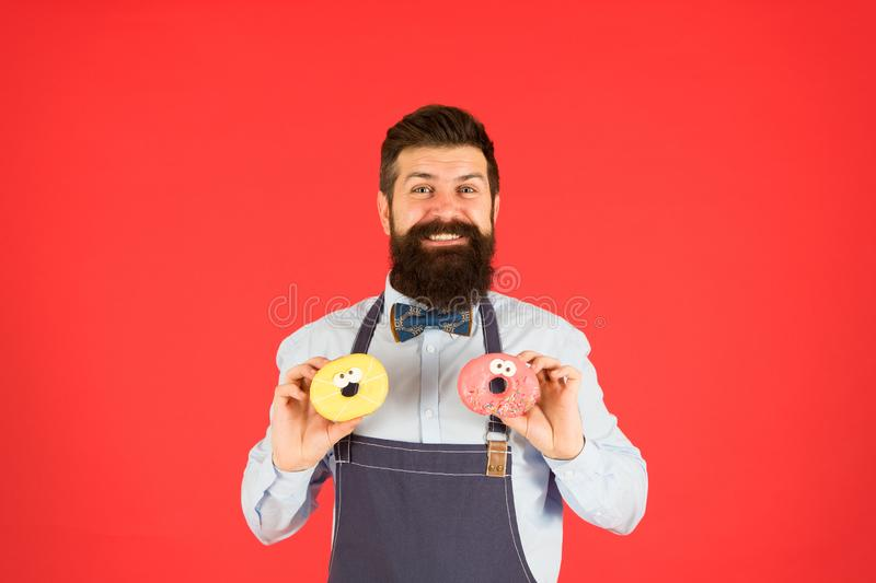 Hipster bearded baker hold donuts. Sweet donut. Waiter in cafe. Doughnut calories. Glazed donut. Bearded well groomed stock photos