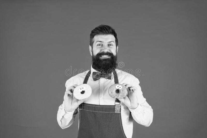 Hipster bearded baker hold donuts. Sweet donut. Waiter in cafe. Doughnut calories. Glazed donut. Bearded well groomed royalty free stock photography