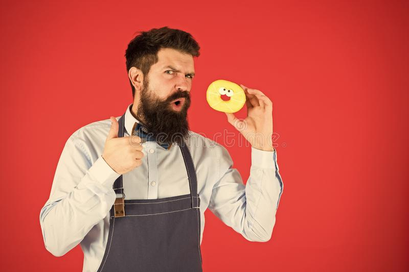 Hipster bearded baker hold glazed donut on red background. Cafe and bakery concept. Sweet donut from baker. Man bearded royalty free stock image