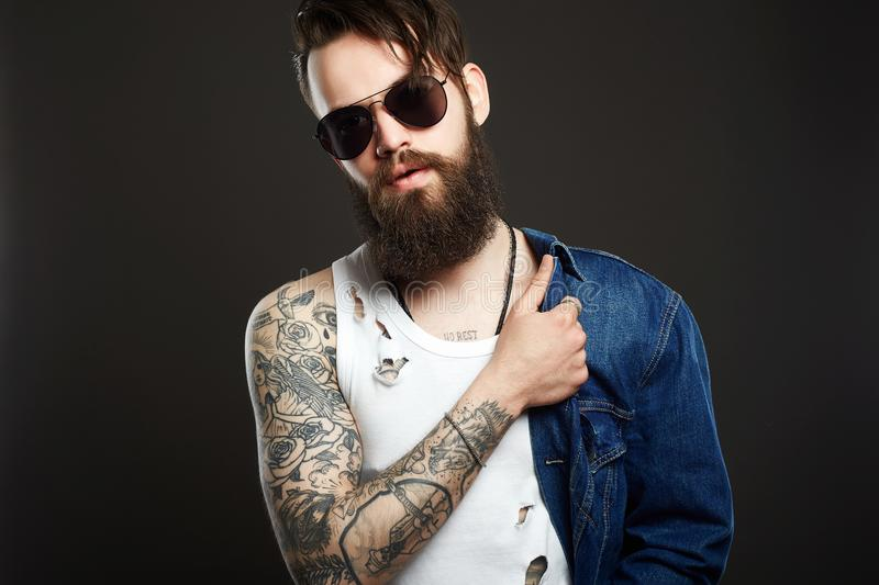 Hipster bearded boy in jeans coat and glasses. Fashionable handsome man with tattoo and sunglasses. Hipster bearded boy in jeans coat and trendy glasses royalty free stock image