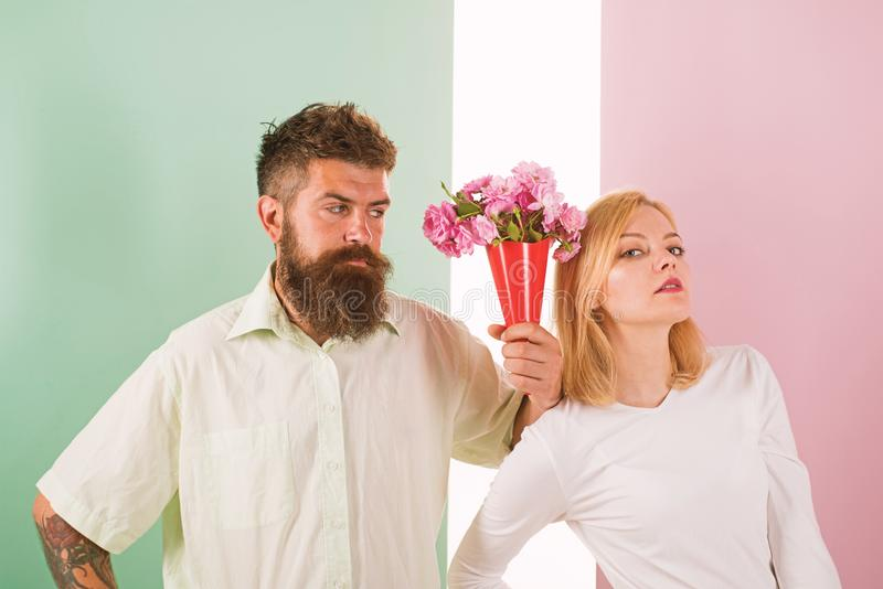 Hipster bearded give bouquet flowers girl excuse gesture. Man with beard apologyes woman. Couple date bouquet flowers stock photo