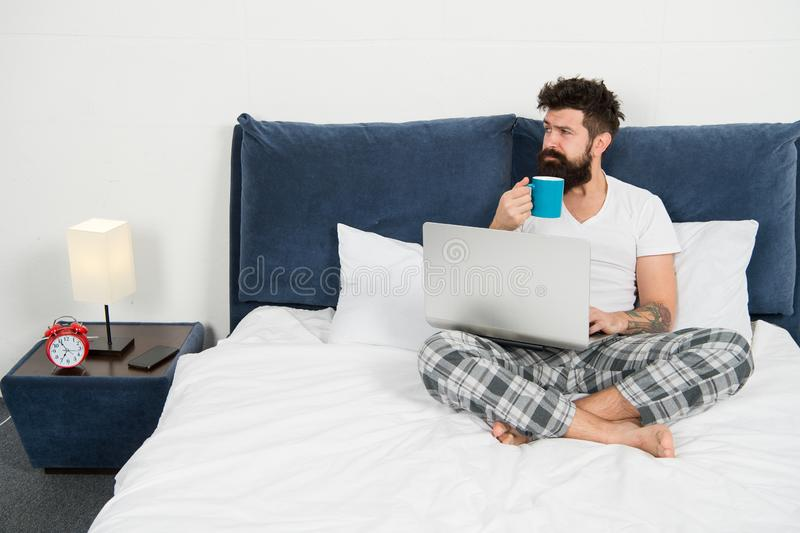 Hipster bearded guy pajamas freelance worker. Remote work concept. Social networks internet addiction. Online shopping stock photos