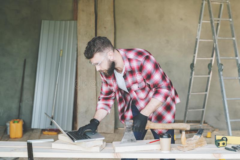 Hipster bearded man is carpenter, builder, designer stands in workshop, using laptop, holding an ax. royalty free stock image