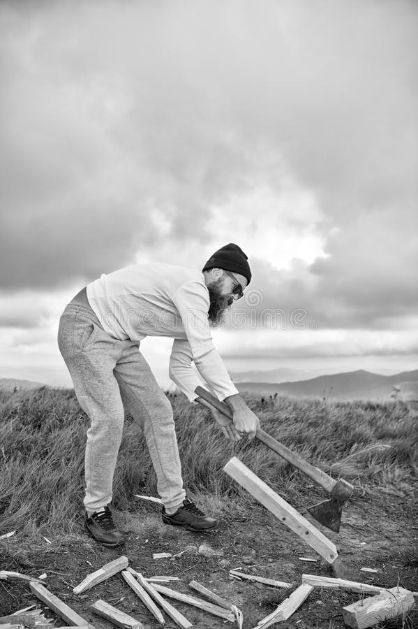 Hipster bearded man chop wood with axe on mountain landscape royalty free stock images