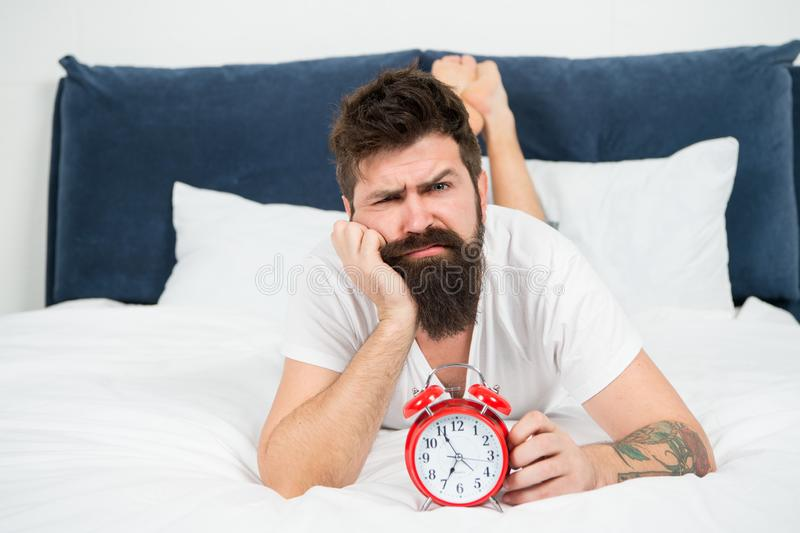 Hipster bearded man lay in bed with alarm clock. Time to wake up. Why you should wake up early every morning. Health. Benefits of rising early. Waking up early royalty free stock photo