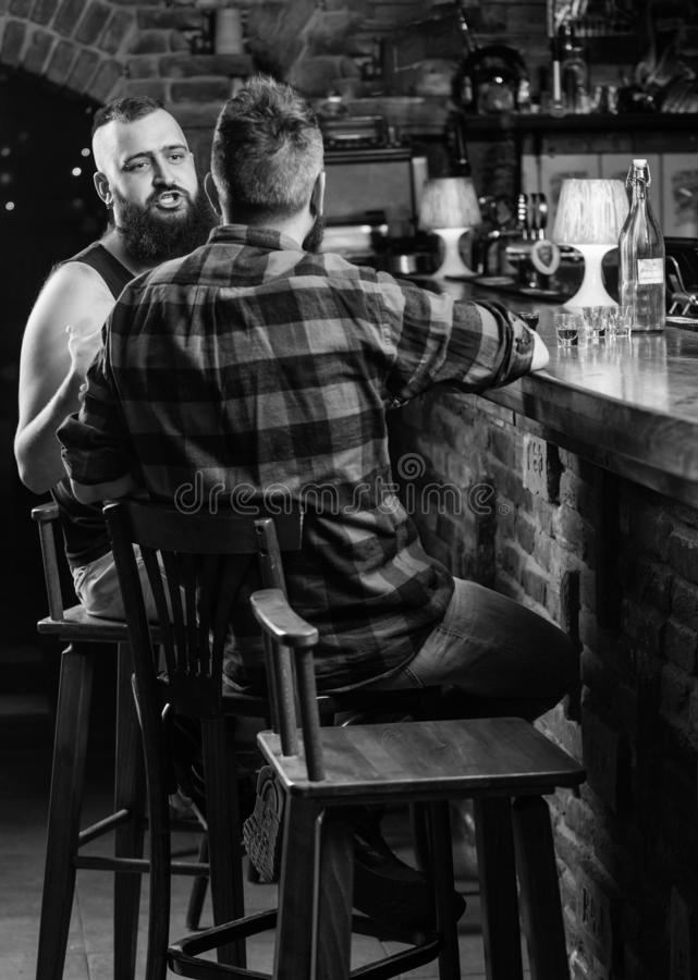 Hipster bearded man spend leisure with friend at bar counter. Strong alcohol drinks. Opening hours till last visitors royalty free stock image