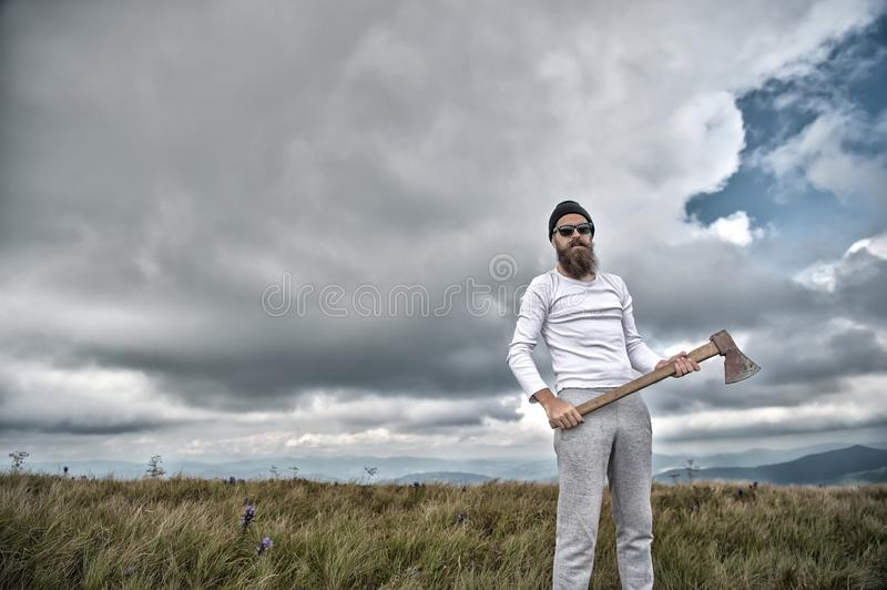 Hipster in sunglasses with axe stand on mountain landscape stock photography