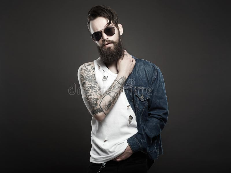 Hipster bearded Stylish boy in jeans and glasses. Fashionable handsome man with tattoo and sunglasses. Hipster bearded Stylish boy in jeans and glasses royalty free stock images