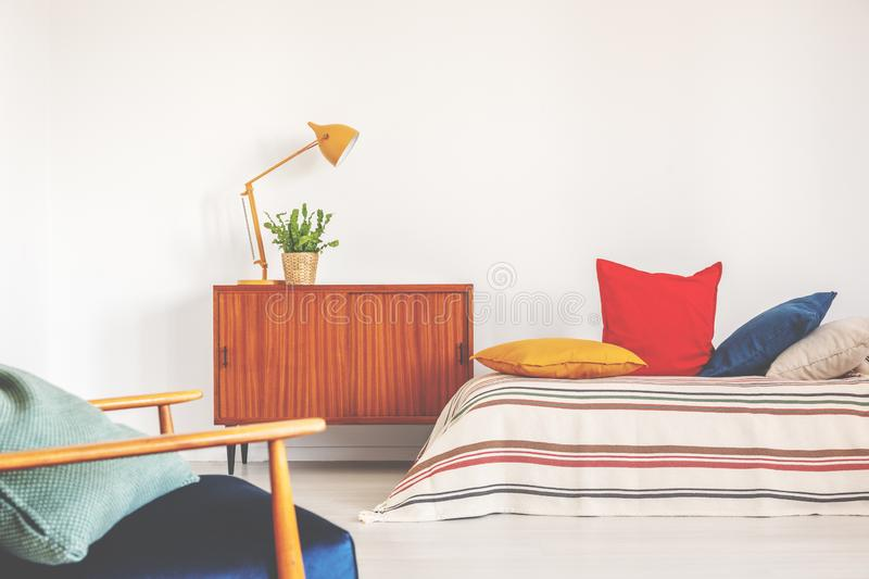 Hipster bedroom with vintage furniture and colorful bedding. Real photo royalty free stock photo