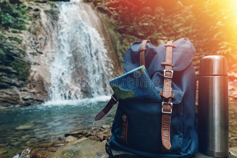 Hipster Blue Backpack, Map And Thermos Closeup. View From Front Tourist Traveler Bag On Waterfall Background. Adventure Hiking Con. Hipster Blue Backpack, Map royalty free stock image
