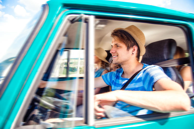 Hipster boy driving an old campervan with teenagers, roadtrip stock photo