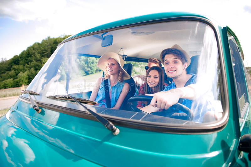 Hipster boy driving an old campervan with teenagers, roadtrip royalty free stock image