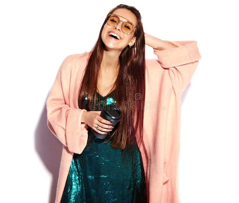 Hipster brunette woman model in stylish pink overcoat and blue evening dress. Beautiful smiling hipster brunette woman model in stylish pink overcoat and blue royalty free stock photography