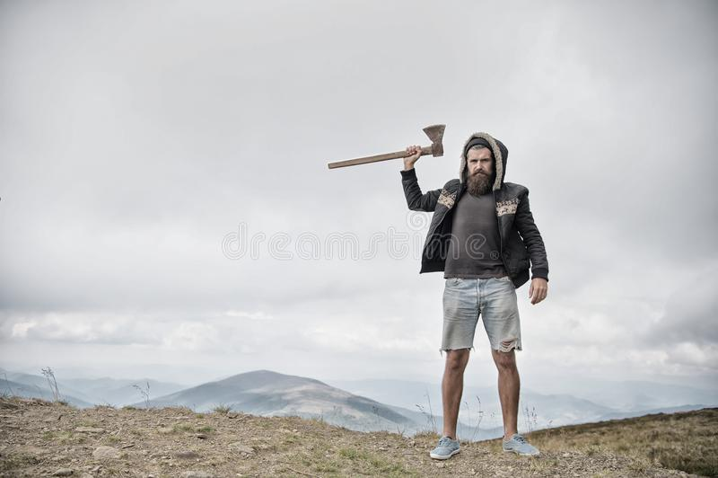 Hipster brutal bearded man with axe stand on mountain top royalty free stock image