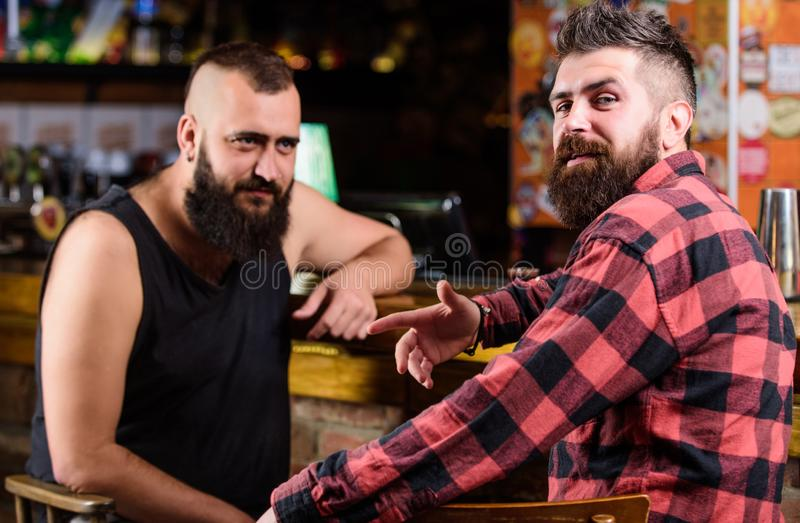 Hipster brutal bearded man drinking alcohol with friend at bar counter. Men relaxing at pub. Strong alcohol drinks. Hipster brutal bearded men drinking alcohol royalty free stock images