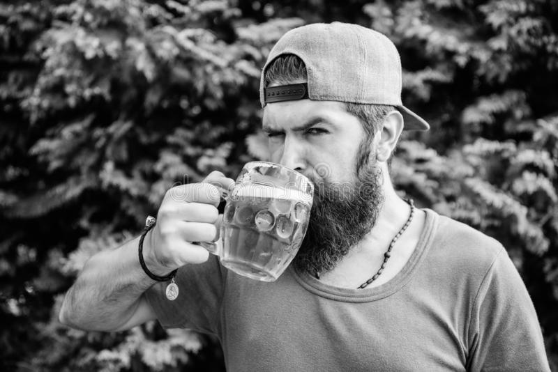 Hipster brutal bearded man hold mug cold fresh beer. Craft beer is young, urban and fashionable. Beer and ale concept. Man relaxing enjoying beer hot summer stock photo